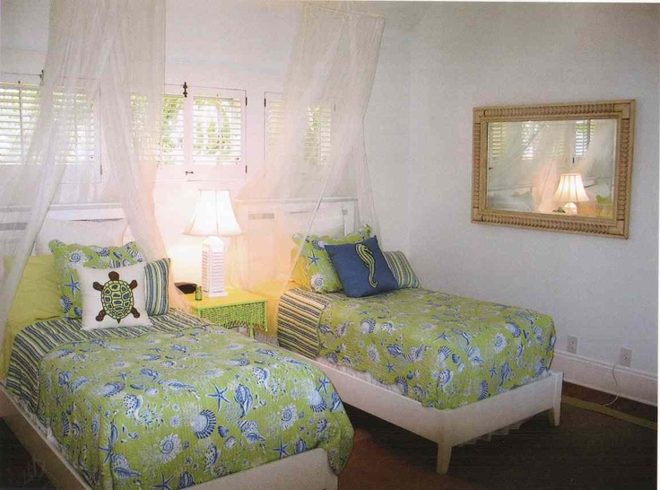 Twin beds separated by a bright colored antique wicker table,  are found in the Beach Theme guest room, upstairs