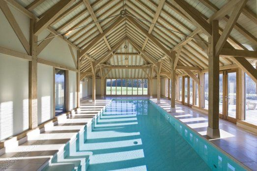 Pool in oak framed building, by Roderick James Architects