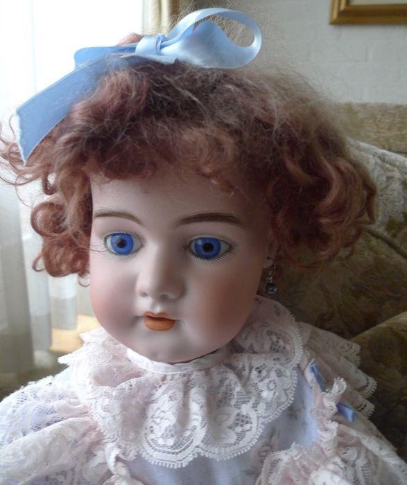Deze mooie  pop is gemaakt door Simon & Halbig en dun gegoten van het mooie blauw/witte porselein waar S&H om bekend staat. Dep bij de Duitse poppen betekent deponiert. De pop is 70 cm Haar hoofd is helemaal gaaf, geen haarlijnen. Haar lijf is in zeer goede staat - nauwelijks speelschade. Haar kop is van een heel mooie kwaliteit blanke porselein. De pop heeft opvallende en mooie blauwe ogen met fijn aangebrachte wimpers. Ze heeft gaatjes in  haar oren en ze draagt oorbellen. Haar vingertjes…