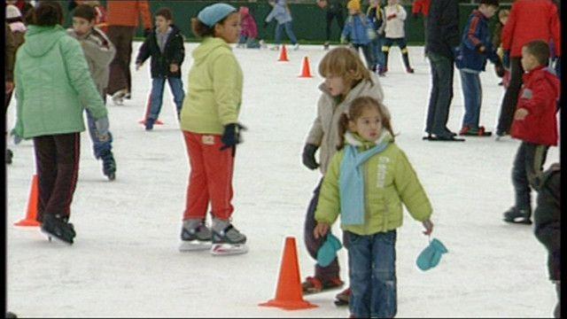 Kinderen gaan schaatsen op een schaatsbaan. Ze gebruiken handige krukjes zodat ze niet vallen. Gelukkig hebben ze lekkere warme kleren aan!