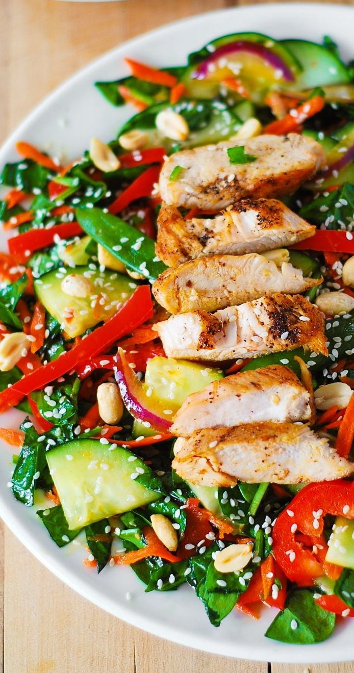 Crunchy Asian Salad with spinach, cucumbers, red bell pepper, carrots, sugar snap peas – all tossed in a delicious, homemade peanut dressing, topped with grilled chicken, toasted peanuts and sesame seeds