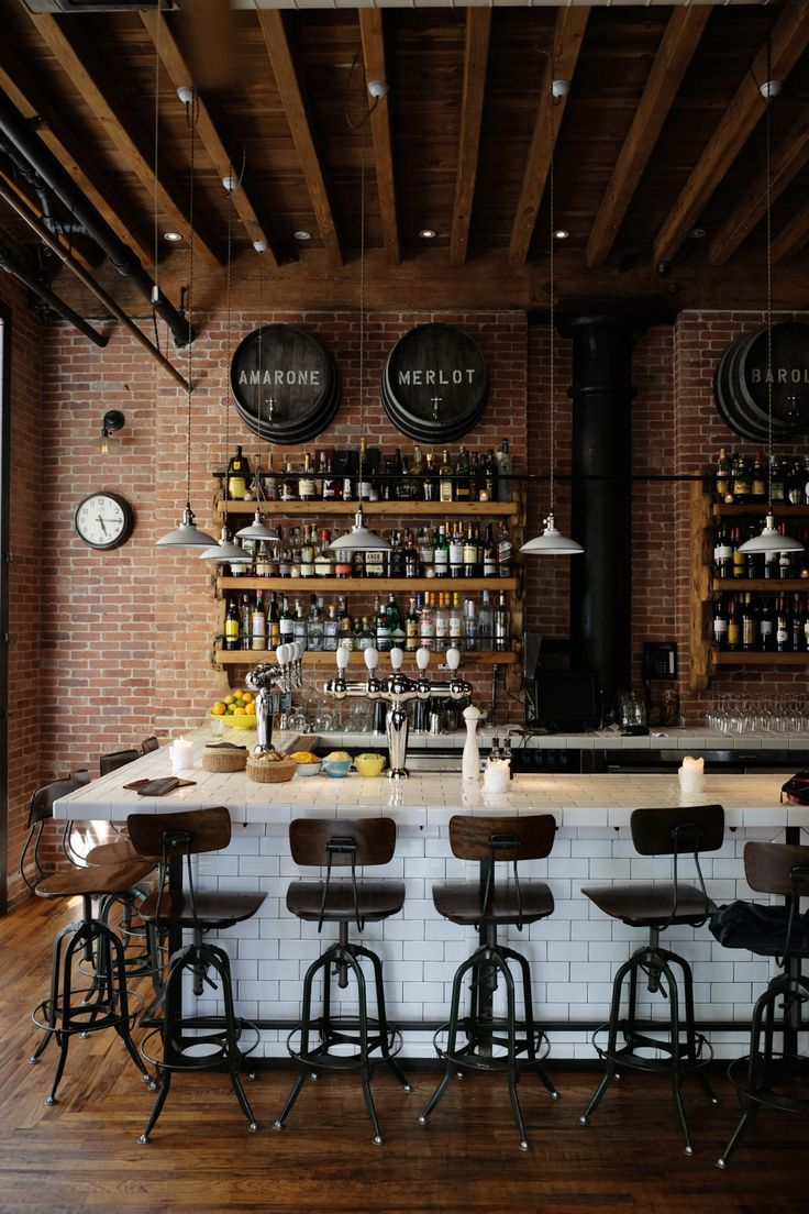 Murs en briques, carrelage et chaises style industiel