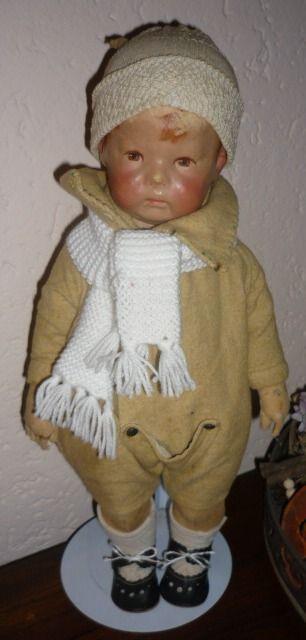 Käthe Kruse pop nr 1  circa 1910/1915 Een mooie vroege Käthé Kruse puppe1 met brede heupen en drie kopnaden. Hij heeft stralen-irissen in zijn bruine ogen en aangenaaide duimen. Hij is volkomen orgineel met Käthé Kruse kleertje. Hij is gemaakt circa 1910/1915, dit is te zien aan de stof die door de verf schijnt. Al met al een mooi bespeelde pop van Käthe Kruse.  Hij is 43 cm groot. Met knuffelschade, maar dat maakt hem juist zo mooi