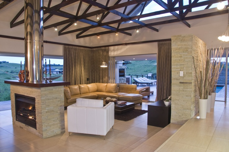 Stone feature wall, indoor fireplace, vase, exposed beams, couch