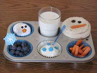 Snowman themed muffin tin lunch! includes powdered donut w/ cchip eyes, glass of milk, circle pbj sandwich w/raisin eyes & carrot nose, blueberries, vanilla yogurt with snowflake sprinkles, and extra carrot noses. Too Cutel!
