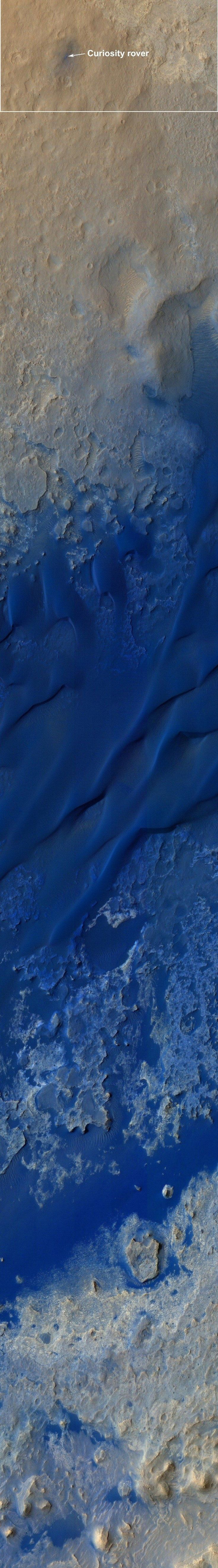 """""""A long strip image from the high-resolution camera on NASA's Mars Reconnaissance Orbiter shows the Curiosity rover's landing spot in Gale Crater, as well as the terrain leading south toward the mountain known as Aeolis Mons or Mount Sharp. The colors have been stretched to emphasize differences in surface composition. A dune field can be seen in deep shades of blue. Beyond the dunes, mesas and buttes are part of the terrain surrounding the 3-mile-high mountain."""""""