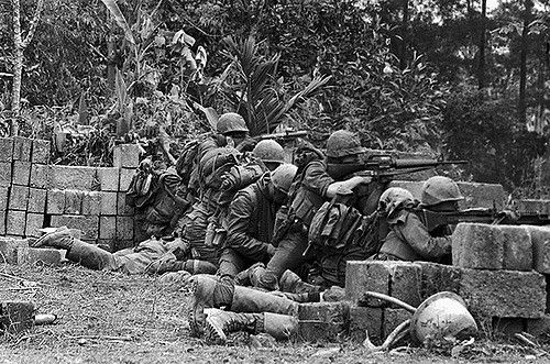 19 Feb 1968, Hue, South Vietnam --- The Battle for Hue:US Marines Crouching Behind Wall 1968 --- Image by © Bettmann/CORBIS