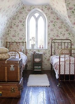 Attic bedroom with floral wallpaper and antique trunks