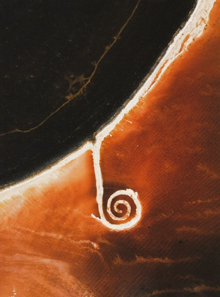 Aerial view of Spiral Jetty (1970), Great Salt Lake, Utah, August 2003. Mud, precipitated salt crystals, rocks and water. Coil: 1500 ft. long and 15 ft. wide. Photographed by David Maisel.