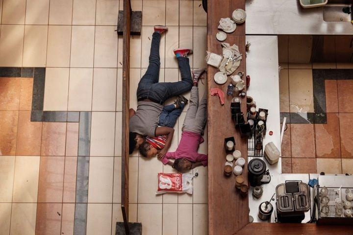 """Tyler Hicks, EEUU, The New York Times 21 Septiembre 2013, Nairobi, Kenia. Una mujer y niños escondidos en el centro comercial Westgate. Salieron ilesos del atentado que llevaron a cabo hombres armados en el exclusivo centro comercial de Nairobi el 21 de septiembre de 2013. 2º premio. Categoría """"Relatos de actualidad"""""""
