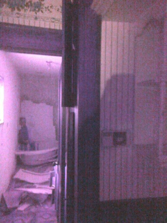 """You can clearly see an apparition standing and facing the wall inside the bathtub. I captured this photo during the """"Red House Investigation"""". This abandoned home was once the murder scene of a family in 1940's."""