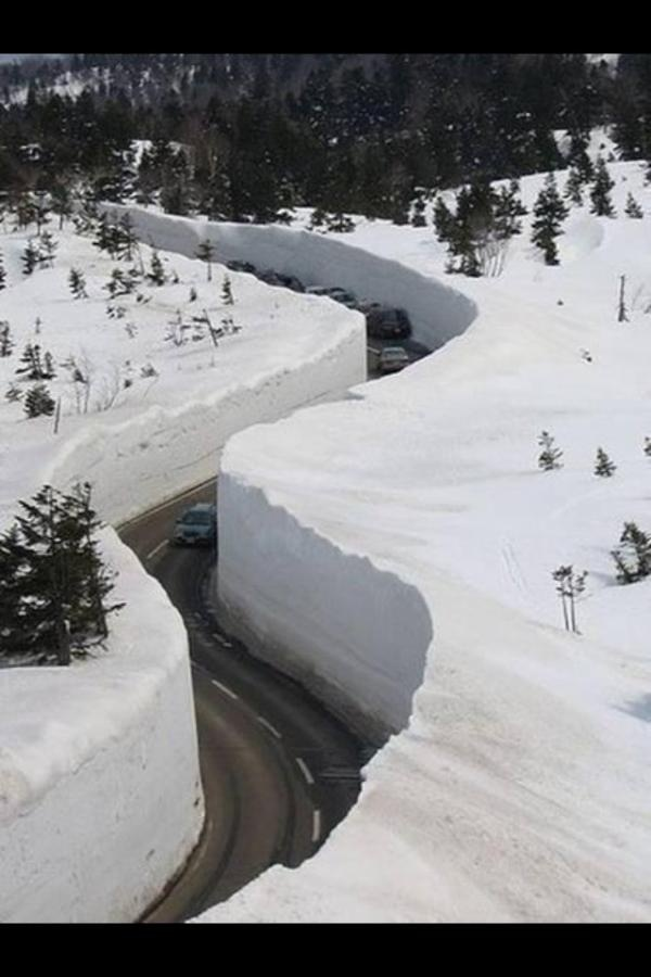 Strasse nach St. Anton am Arlberg, Vorarlberg, Austria - black asphalt path carved thru deep white snow