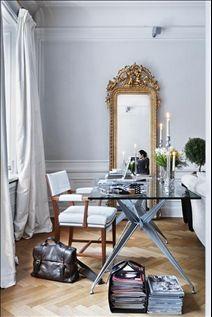 Arbetsbordet är placerat vid fönstren med utsikt över vardagsrum och matsal. Bordet är ritat av Philippe Starck och karmstolen, i form av Josef Frank, ett unikt exemplar i vitt lackskinn. En antik guldspegel vilar tungt på golvet.