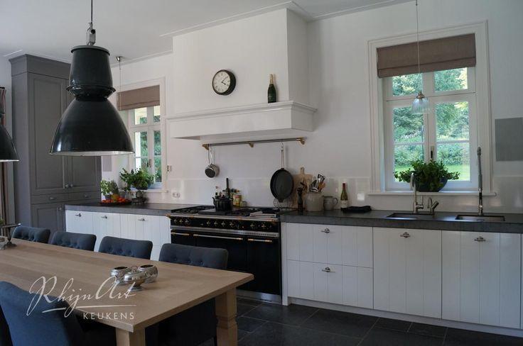 Ruime woonkeuken met tafel in het midden, groot aanrechtblad onder het raam, met goede verlichting erboven (spotjes?)