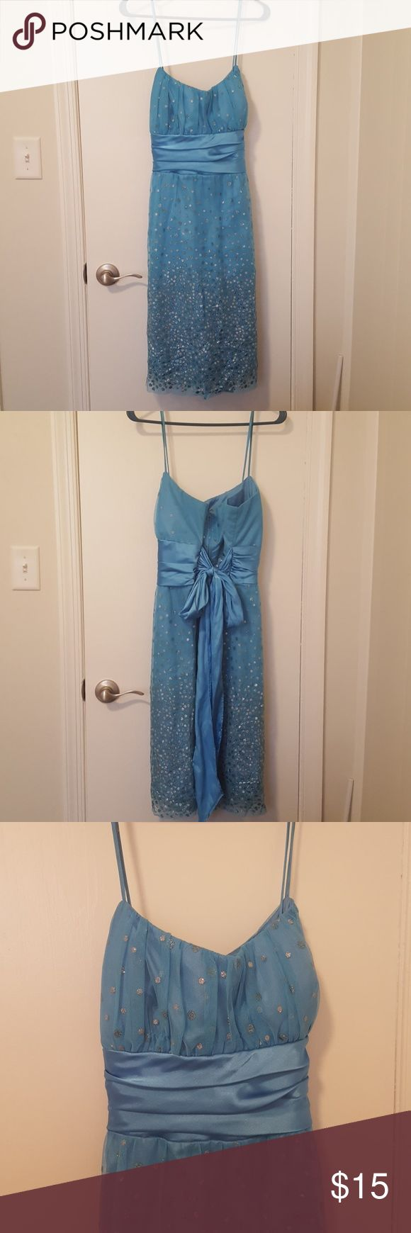 Formal Dress The dress is an aqua blue color with a silver & blue glitter polka dot overlay. It has a ruched detail waist that wraps around and ties in the back. It has a zipper closure. Masquerade Dresses Prom