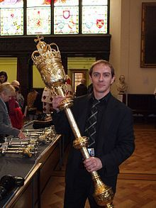 Ceremonial mace - A court official holds the mace of the Lord President of the Court of Session, during a Doors Open Day. This mace is also known as the Old Exchequer Mace. Made in London in 1667, of silver coated with 24 carat gold, and weighing 17 pounds, it carries the monogram C.R. for the then monarch Charles II..