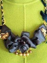 Feito em fita de cetim azul escuro e pérolas douradas.