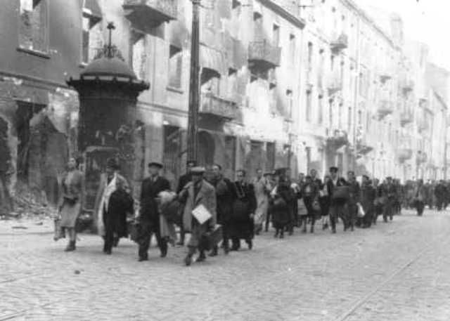 Jews rounded up during the Warsaw ghetto uprising are forced to march to the assembly point for deportation