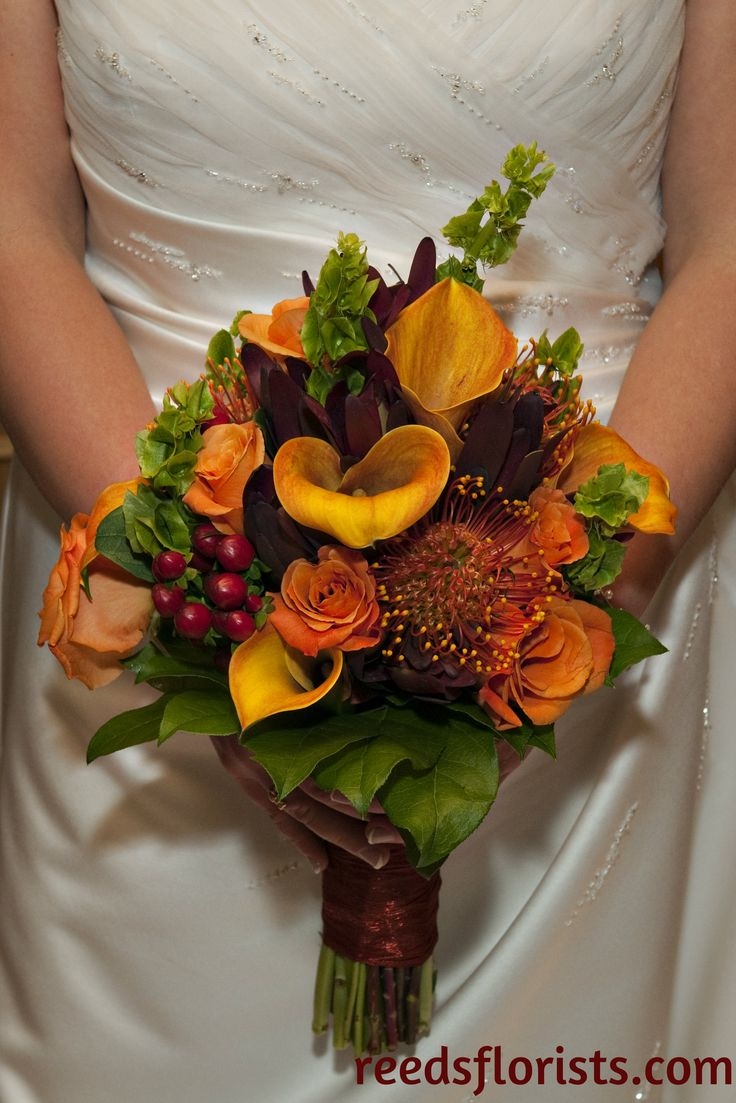 Beautiful fall wedding bouquet. Orange calla lilies and roses, pincushions, ginger and hypericum. Perfect for a bride who loves fall colours! reedsflorists.com