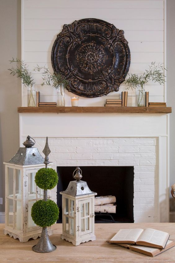 HGTV Fixer Upper hosts Chip and Joanna Gaines painted the original fireplace brick white and added shiplap paneling and a natural wood mantle. The living room is dressed with French Country accessories, books and topiaries.