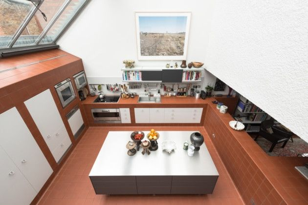 Light floods the double-height kitchen from sloping skylights