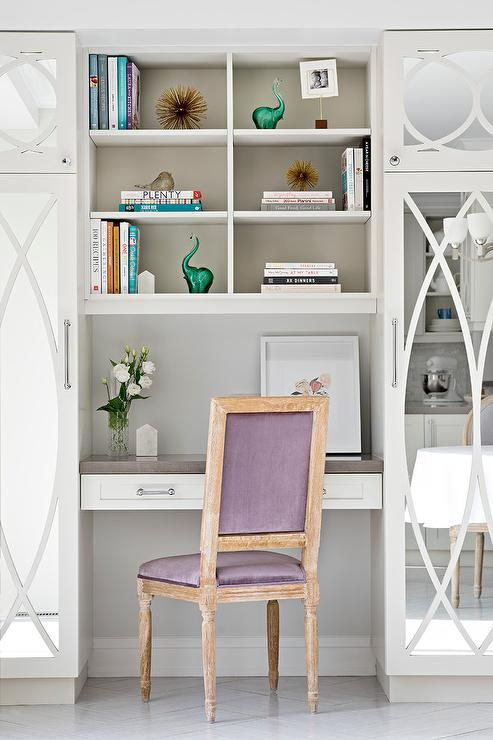 Flanked by mirrored mullion cabinets, this beautiful designed work space features a white bookcase fixed above a white floating desk fitted with polished nickel drawer pulls and a gray countertop seating a purple velvet square back French desk chair.