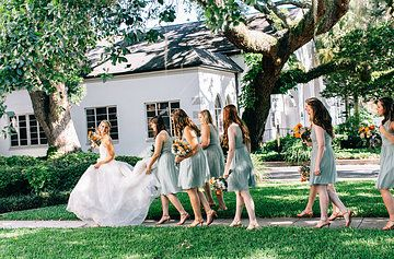 time to head to the chapel, the bridesmaids follow the bride  in pale mint green carrying their spring green and peach bouquets.
