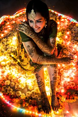 Mehendi Designs - Beautiful Bridal Hand and Feet Mehendi | WedMeGood | Intricate Mehendi Design on Hands with Motifs on Arms and Peacock and Jaal Mehendi on Feet with the Bride Wearing a Mehendi Green Printed Suit and a Gold Maang Tikka Picture Courtesy: Chetna Sarin Photoart #mehendi #flowers #wedmegood #lights