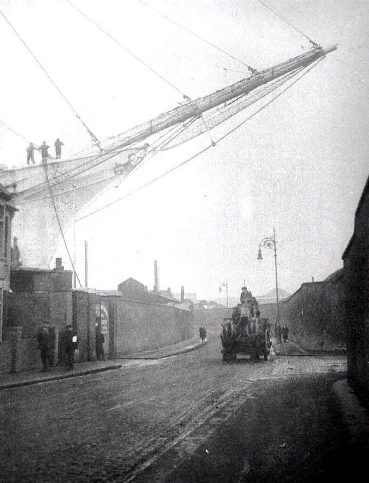 The ghostly bowsprit of a mighty sailing ship projects over the wall of Union Wharf Lower Dock in the East End