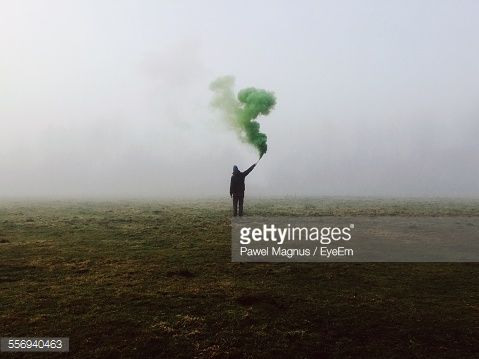 Stock Photo : Rear View Of Man Holding Smoke Bomb On Field In Foggy Weather