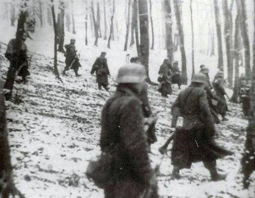 German troops cautiously approach American lines in the early morning hours of December 16, 1944.