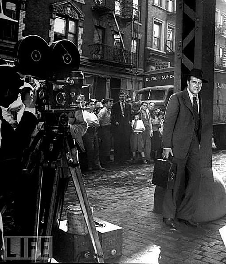 "Ray Milland, leaning on a Third Avenue El post, filming ""The Lost Weekend"" in NYC in 1945. Neighborhood residents are watching the process. His character, Don Birnam, walks up Third Avenue for many blocks, looking for an open pawn shop to pawn his typewriter so he can buy booze. He finds them all closed because it's Yom Kippur."