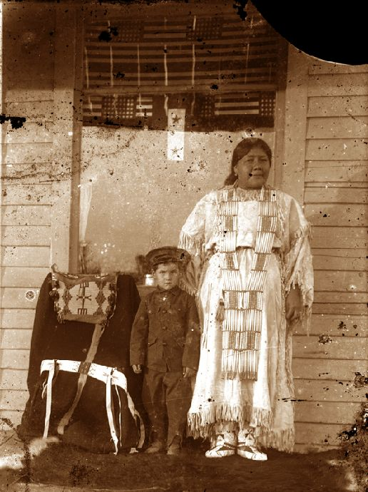 Unidentified Native American woman. Notice in the background, the American flags serving as window coverings as well as the old saddle and blanket to the left
