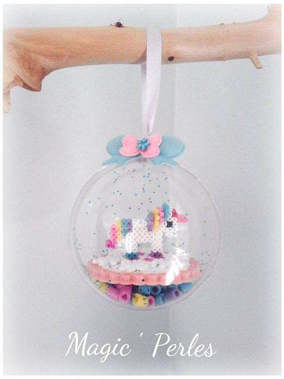 Boule MagiCorn boule de 6 cm en plastique où se trouve à lintérieur une petite licorne en 3D réalisée en mini perle hama fixée sur un flocon de neige en mini perle hama. Le tour du socle en perle sillumine dans le noir grâce aux perle phosphorescentes qui donne un halo rose Un ruban de