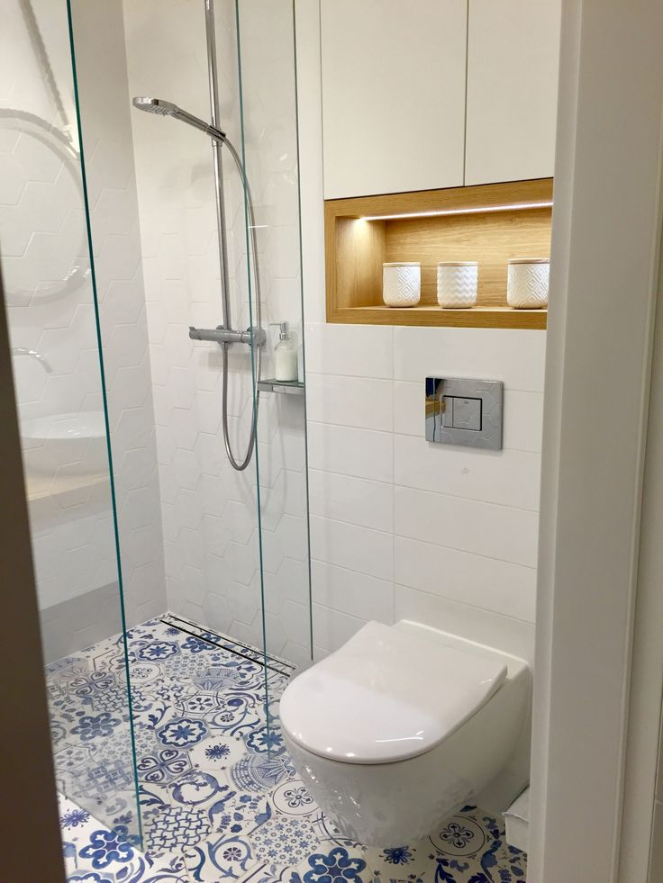 White hexagonal and rectangular tiles. Blue decor hexagonal floor tiles. Wooden shelf with led lights. Modern shower.