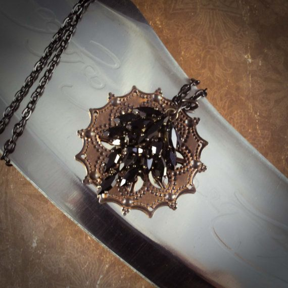 """The highlight of this Goth inspired necklace is a vintage black rhinestone arrangement set against a filigree copper medallion. This cluster is hanged (excuse us, we mean hung) on a silver 22"""" double chain. A dark and lovely design! 091808SNH"""