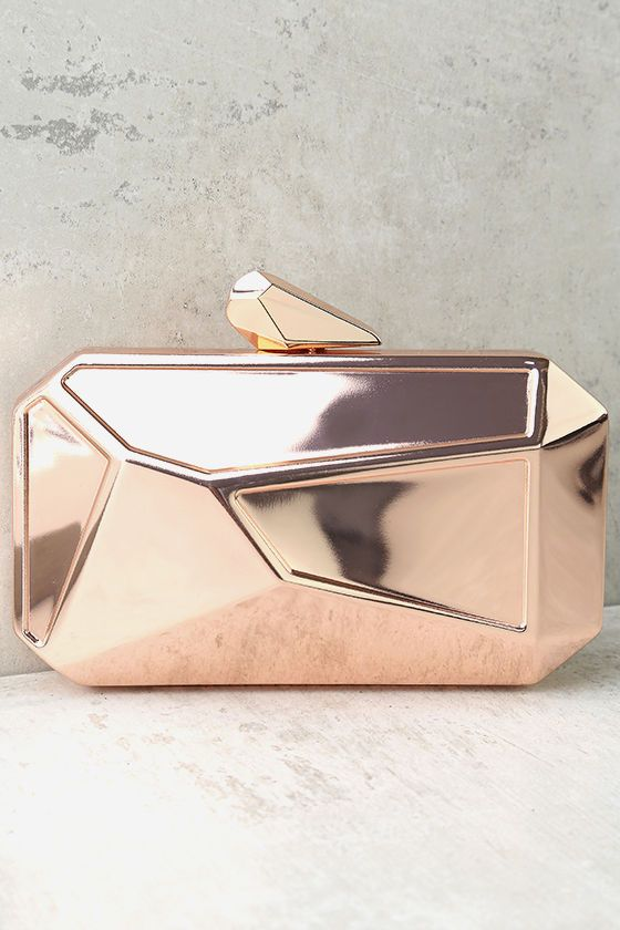 "Get noticed with the What a Rock Rose Gold Clutch! Shiny rose gold metal shapes this faceted box clutch with a matching clasp closure. Interior (with accordion sides) has just the right amount of room for all your essentials! Carry as a clutch or attach the 46"" long rose gold chain strap."