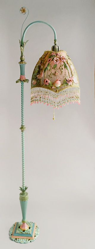 Antique bridge (reading) lamp with an unusual tendril and flowers accent has been hand painted and holds a hand-dyed Sleeping Beauty shadowbox lampshade. The silk shade is ombré dyed from ballet pink to dusty robins egg blue and has a confection of antique textiles in tones of pink, green, silver and gold. The antique fabrics include antique gold metallic lace, overlaid with beautiful Victorian-era appliqués of pink roses!  $ 3,000 +