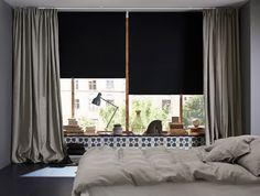 Ein Schlafzimmer, u. a. mit schwarzen Verdunklungsrollos vor den großen Fenster und einer Schicht blickdichten, grauen Gardinen.