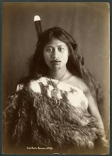 Rotorua, New Zealand. Young Maori woman with moko, wearing a kahu huruhuru (feather cloak), a huia feather in her hair, and a hei tiki (neck pendant), 19th century.