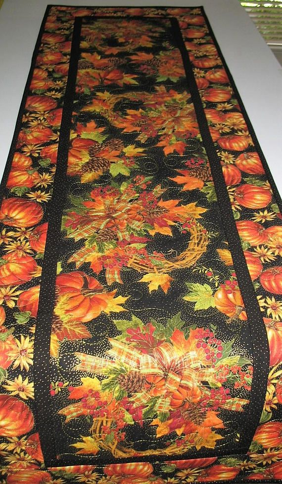 Fall Table Runner quilted focus fabric from Timeless Treasures Measures 49.5 x 15 inches Made by Chris This gorgeous autumn fabric runner has gold filament throughout to add shimmer. The focus fabric is from Timeless Treasures. I absolutely love this fabric. Colors in brilliant oranges, yellows, deep browns, golds,and greens. It has been free motion quilted in a loopy meandering style in the center and outside border with beautiful gold embroidery thread. The batting is from Warm and…