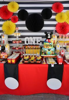 It's a Mickey Mouse 1st Birthday Party! Black and white striped backdrop, Mickey silhouette, suspenders and lots of sweet treats.