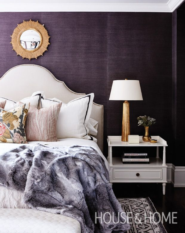 Deep plum-colored wallpaper envelops this bedroom in a rich, regal hue, which is played up by the gold accents and the headboard's brass nailhead trim. | Photographer: Angus Fergusson | Designer: Allison Wilson, Sarah Richardson Design