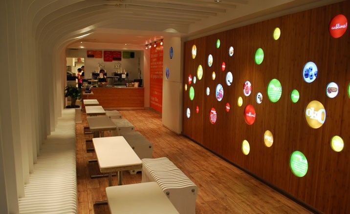 That's a fun back-lit wall, with colored acrylic details.  Also, not your average yogurt shop design.