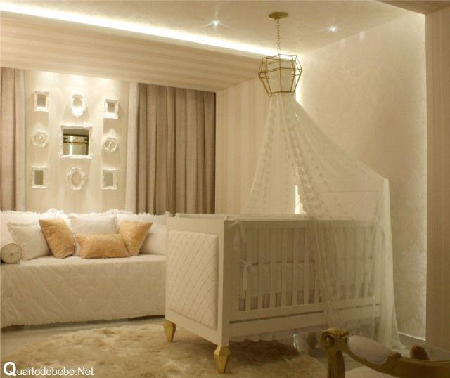 Berço branco com pés dourados com mosquiteiro fixado por dossel de teto.
