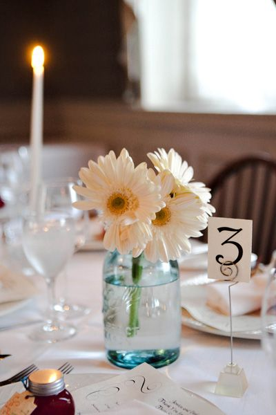 gerbera daisy centerpieces. what about this idea for the wedding @KaitlynHyde09 and maybe you can help me paint them dark blue and gray? or should we just leave them clear?