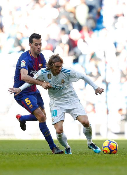 Luka Modric of Real Madrid is challenged by Sergio Busquets of Barcelona during the La Liga match between Real Madrid and Barcelona at Estadio Santiago Bernabeu on December 23, 2017 in Madrid, Spain.