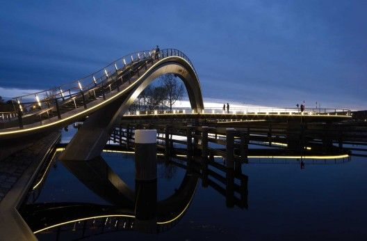 Melkwegbrug / NEXT Architects | ArchDaily - Bicycles and remainder traffic cross the bridge using the 100m long bicycle deck. This deck was designed as a pendulum over the water, so that the slope could be limited to a minimum. Because pedestrian traffic was separated from cyclists, the direct line between the Melkweg-road and city centre could remain. Furthermore the 48m arch remains the fastest possible way to cross the water.