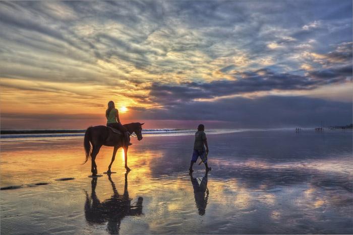girl riding horse at sunset