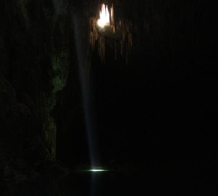 Feixe de luz corta o Abismo Anhumas iluminando o lago. O local se encontra no município de Bonito, estado do Mato Grosso do Sul, região Centro-Oeste do Brasil. É um dos locais mais lindos de Bonito, para onde se faz uma verdadeira viagem ao centro da terra - uma descida de 72 m em rapel, por uma fenda na rocha, que leva a uma caverna com magníficas formações e um lago de águas cristalinas onde pode-se flutuar e ver reveladas as belezas subaquáticas do lugar.  Fotografia: Lauro Sirgado.